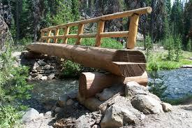 usfs trail crew builds a log bridge over fall creek at green lakes trail head