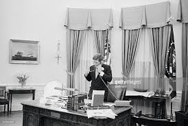 john f kennedy oval office. president john f kennedy stands behind his desk in the oval office as he talks i