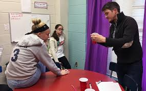 justin hicks of yes appalachia uses red solo cups to help brelyn sturgill left and aubry spaulding work out a math story about saline solution