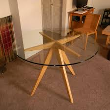 round glass dining table with wooden legs
