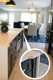 Black painted kitchen island with waterfalling Hanstone quartz counters and  concealed outlet. | VillageHomeStores.