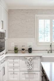 Stunning kitchen features white shaker cabinets paired with Luminous  Calacatta Marble and a white linear tiled backsplash under light gray  grasscloth ...
