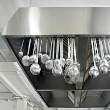several kitchen strainers in hanging from a typical restaurant kitchen hood