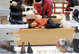 a young girl lies on a couch as the woman she was accompanying checks out shoes