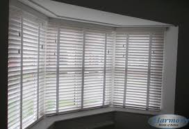 white wooden blinds with tapes in a bay window