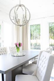 chic dining room features a gray pedestal dining table lined with white wingback dining chairs illuminated by a polished nickel sphere pendant surrounded by