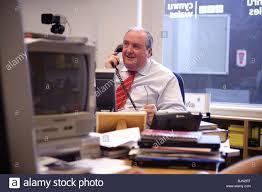 office radio. A Male Journalist On The Telephone Working In BBC Radio Wales / Cymru Newsroom Office And Studio, Aberystwyth UK I