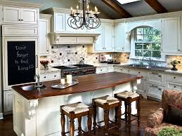 Red Brick Herringbone Cooktop Backsplash with oversized lantern pendants  and white cabinets with hood in kitchen (brick & lighting)