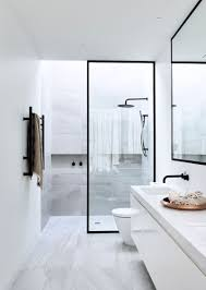 the black frame around the glass of this shower matches the black frame around the mirror as well as the black hardware used throughout the rest of the