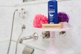 cake stand on top of a bathtub and storing loofahs nivea in shower
