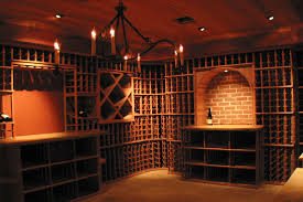 exposed brick wall accents the lighted arch in this very stylish 2 500 bottle newton wine cellar the redwood beadboard pan ceiling and chandelier details