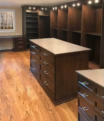 his hers master walk in with two closet islands custom lighting and a closet desk