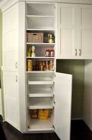 tall white corner kitchen cabinet pantry with pull out shelves combined with green kitchen wall