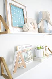 stuffed animals books letters and picture frames can all be used to decorate nursery shelving choose items that color coordinate with your nursery or