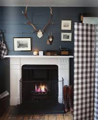 from stanley our contributing market editor blue planked walls fireplace antlers and a gingham folding screen love this clever to go dark on the