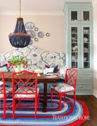 traditional home this breakfast room bines country elements like a braided rug and wood table with red lacquered chinese chippendale chairs and a bench