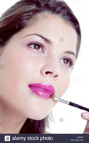 female brunette hair pink eye shadow and pink eye liner applying bright pink lipstick to lips black and silver lip brush