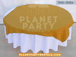 round table with white table cloth and gold overlay runner