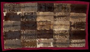 a rug made of 25 skins stitched on to a red fabric backing
