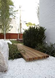 a short walkway made from stained wood strips connect two diffe parts of the yard in a modern contemporary way