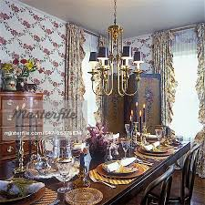 dining room close up of dining table in foreground antiqued brass chandelier with black shades cascade of flowers on folding screen jacobean fl