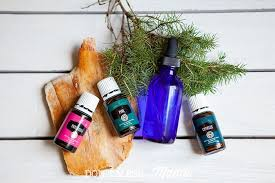 closeup of pine patchouli and cypress essential oils and a blue glass dropper bottle with