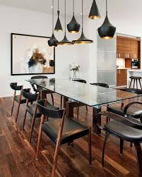 wooden floor wooden chairs black leather cushions glass table wooden legs large wall art piece sculptural black sahde pendant lamps