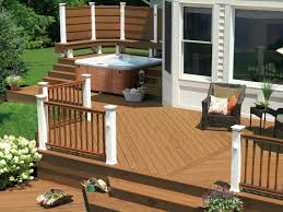 wooden deck with patio and corner hot tub with bence and privacy screen plus
