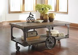 from ashley s rustic accents collection this rustic wheel cocktail table is inspired by a factory