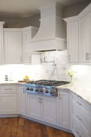 White shaker cabinets, decorative range hood, inset cabinet .