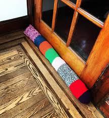 multi colored knit door snake on wood floor diy insulation