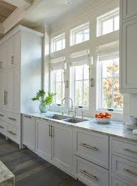 lighting over kitchen sink. the light gray kitchen cabinets are adorned with extra long satin nickel pulls a stainless steel dual sink stands under row of windows dressed in lighting over