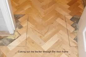 installation of new parquet block flooring herringbone design with double block boarder