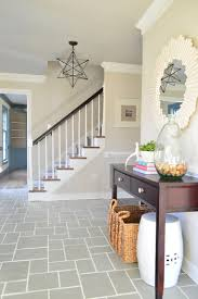 foyer entryway with gray slate tile floor and clean white grout lines including pretty mirror and