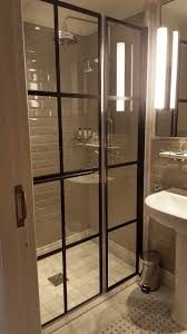black grid style pivot shower door with inline panel at the prestigious russel hotel in london