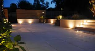 garden lighting designs. slate grey garden lighting downlighters on a wooden clad wall in newly designed and landscaped designs