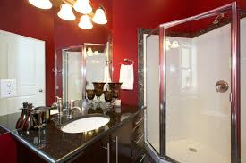black and red bathroom accessories. white toilet and laminate flooring mirror also wooden chair red wall table with chandelier as well black bathroom accessories