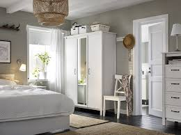 A small bedroom furnished with a wardrobe with two white doors and one  mirror door.