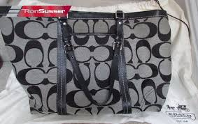 I am pleased to offer this Authentic Coach Signature Gallery Large Tote .  Style is K08659 F13096. Very stylish in silver fabric with black leather  trim.