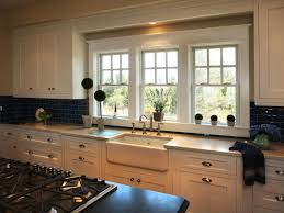 small bay window above kitchen sink gray cut pile rug gray tile backsplash fabric seat and