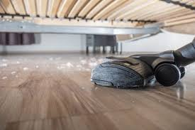 a vacuum s up dust on a hardwood floor under a bed
