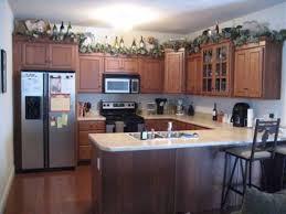 image of martha stewart decorating above kitchen cabinets with bottle