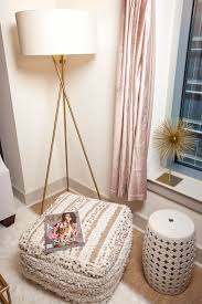 the darling detail s living room features a west elm mid century tripod floor lamp a herringbone metallic wool pouf and a mercer41 warwick lacey garden