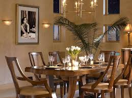 this warm dining room makes use of natural light with geometric windows and artificial light with a candlelight chandelier a simple flower arrangement of