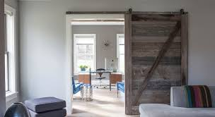 contemporary home office sliding barn. living room with distressed barn door opening to reveal gray home office midcentury sunburst clock hung on wall behind a modern walnut veneer computer contemporary sliding l