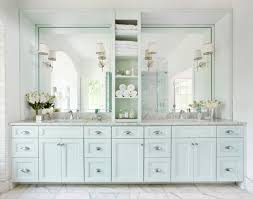 bathroom double vanity with center tower. master bathroom with light blue double vanity paired white carrera marble countertop and framed mirrors over tiled floor. center tower i