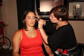 woman in red sitting in a chair while make up is applied to her eye