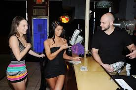 Averi Brooks from RealityKings Wearing Black Dress in Bar Giving.