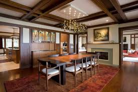mid century modern dining room with brown rug medium toned wooden floors a chandelier lamp white