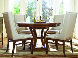small round wood dining table with four upholstered wingback chairs set a gallery of cozy